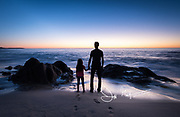 A father and daughter hold hands and watch the sunrise over the Pacific Ocean together.