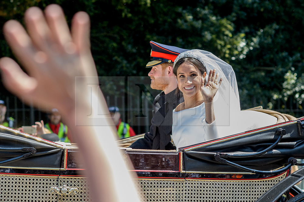 © Licensed to London News Pictures. 19/05/2018. London, UK. An open top carriage carrying Prince Harry and Meghan Markles leaves the chapel to make its way through Windsor. Guests arrive at The wedding of Prince Harry, The Duke of Sussex to Meghan Markle, The Duchess of Sussex, at St George's Chapel in Windsor. Photo credit: Andre Camara/LNP