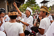 Apr. 25 -- UBUD, BALI, INDONESIA:  A holy man blesses members of the orchestra at the funeral for Cokorde Gede Raka, a member of Ubud's royal family Sunday, Apr. 25. Balinese are Hindus and cremate their dead. Balinese funerals are elaborate - and expensive - affairs. A funeral for one person costs a minimum of 45 million rupiah (about $5,000 US). The body is placed into the bull's body at the cremation and cremated in the bull. The funeral pyre is burnt adjacent to the bull. That is what a family may earn in two to three years. The result is that only the rich can afford formal cremations. The body (in the casket) is placed in the top of the funeral pyre and the procession takes the body to the cremation site. The funeral pyre, and the body, are spun at intersections to confuse the spirits so the soul doesn't try to return to its home and to confuse evil spirits.    PHOTO BY JACK KURTZ