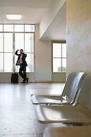 Business man using mobile phone by window in airport