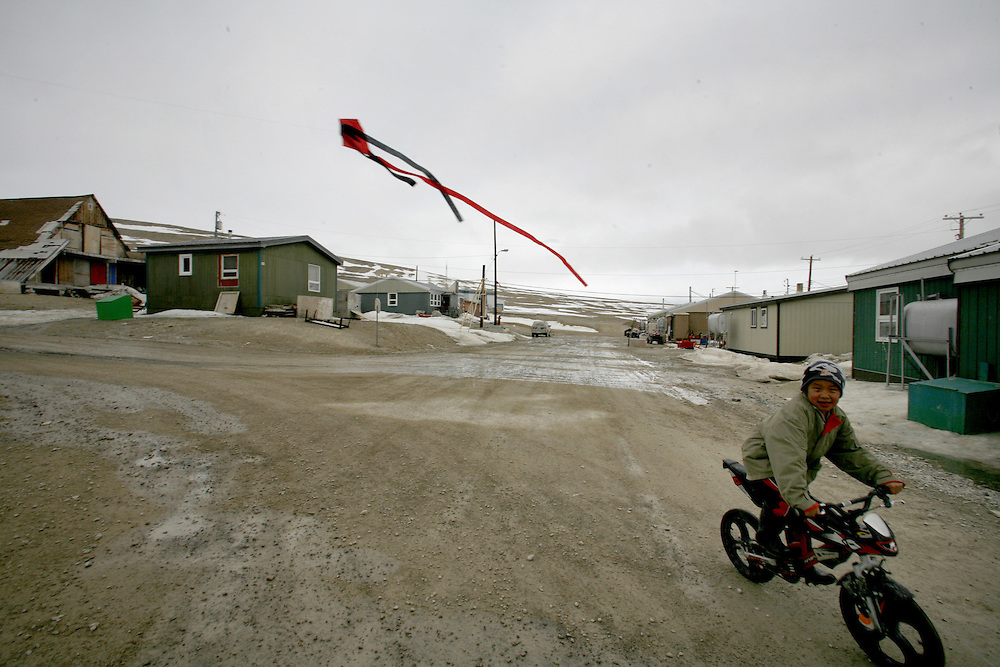 A young Inuit boy rides his bicycle outside in the constant summer light in the Inuit town of Resolute Bay, located in the far North of Canada, on Thursday, June 14, 2007. ..... **GERMANY OUT**