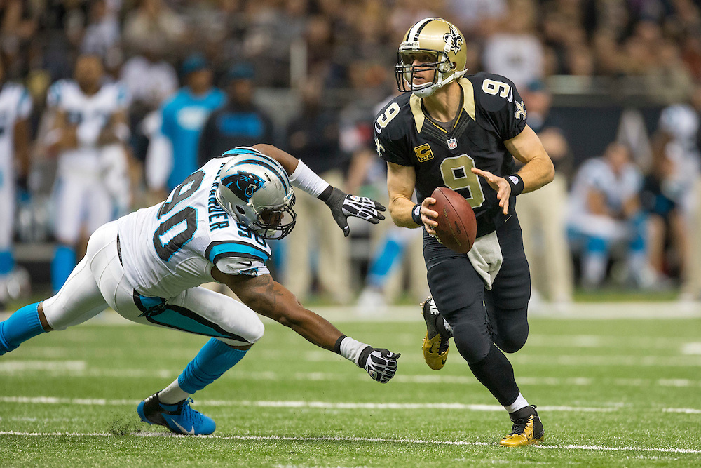NEW ORLEANS, LA - DECEMBER 30:  Drew Brees #9 of the New Orleans Saints rolls out to get away from Frank Alexander #90 of the Carolina Panthers at Mercedes-Benz Superdome on December 30, 2012 in New Orleans, Louisiana.  The Panthers defeated the Saints 44-38.  (Photo by Wesley Hitt/Getty Images) *** Local Caption *** Drew Brees; Frank Alexander