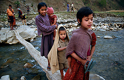 "RUKUM DISTRICT, NEPAL, APRIL 15, 2004:  Children cross a bridge made out of logs in Rukum district April 15, 2004. The infrastructure of Western Nepal is nonexistant and givernment troops have a hard time manoevering through the difficult terrain to combat the growing Maoist insurgency. Analysts and diplomats estimate there about 15,000-20,000 hard-core Maoist fighters, including many women, backed by 50,000 ""militia"".  In their remote strongholds, they collect taxes and have set up civil administrations, and ""people's courts"" to settle rows. They also raise money by taxing villagers and foreign trekkers. Though young, they are fearsome fighters and  specialise in night attacks and hit-and-run raids. They are tough in Nepal's rugged terrain, full of thick forests and deep ravines and the 150,000 government soldiers are not enough to combat this growing movement that models itself after the Shining Path of Peru. (Ami Vitale/Getty Images)"