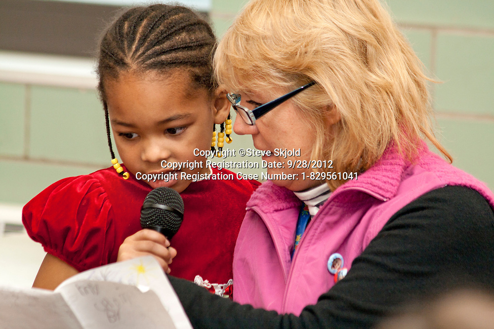 Teacher working on class presentation with black African American student age 5. Expo Elementary School St Paul Minnesota MN USA