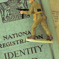 Lead model of Allied Forces soldier in desert fatigues aiming semi-automatic rifle and lying on British Identity Card of World War 2