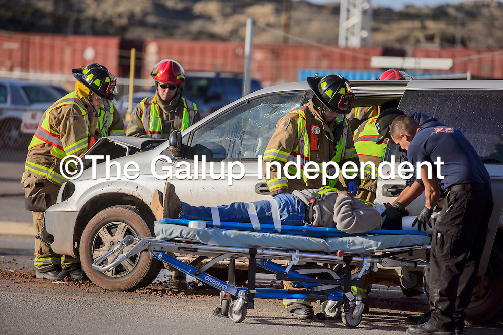 Gallup firefighters remove one victim from a vehicle at the site of a crash that diverted traffic on east Historic Highway 66 in Gallup Friday.