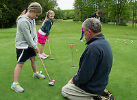 Avery Marshall lines up her putt with her sister Camryn looking on during their golf lesson with Randy Annis at Bolduc Park Tuesday evening.  (Karen Bobotas/for the Laconia Daily Sun)