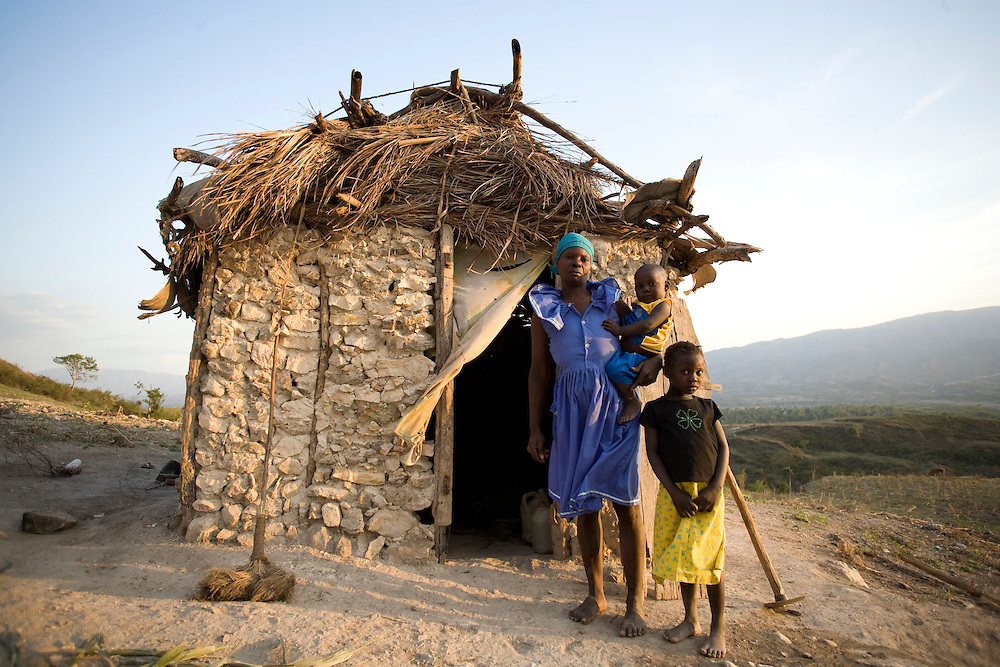 A woman with two children stand in front of their home on a mountainside.