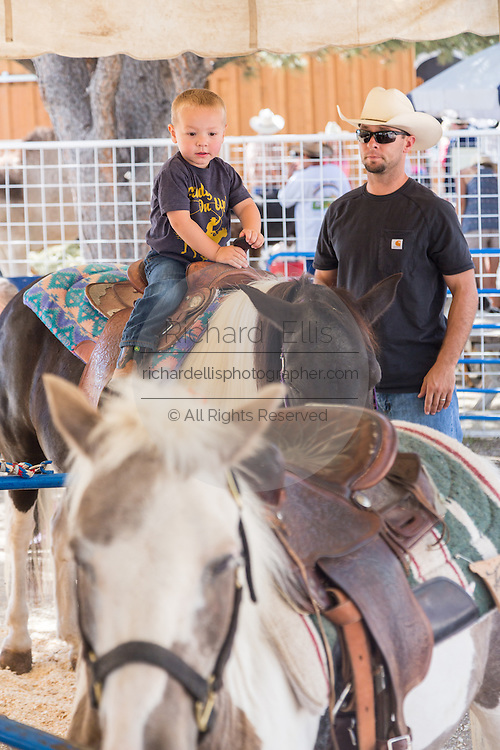 A young boy rides a pony under the watchful eye of his father during Cheyenne Frontier Days July 25, 2015 in Cheyenne, Wyoming. Frontier Days celebrates the cowboy traditions of the west with a rodeo, parade and fair.