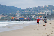 Two people running at the beach towards the Santa Monica Pier with a seagull flying by. Santa Monica Beach, 5.27.17 CA.