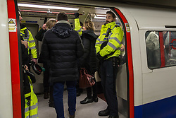 London, December 31 2017. Police officers ride the Bakerloo Line as revellers head in to London's West End enjoy the build-up to New Year. © SWNS
