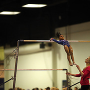 A young gymnasts performs on the uneven bars aided by her coach during competition at the 21st American Invitational 2014 competition at the XL Centre. Hartford, Connecticut, USA. USA. 31st January 2014. Photo Tim Clayton