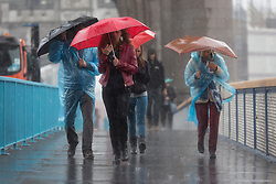 © Licensed to London News Pictures. 26/08/2014. London, UK. People walk with umbrellas on Tower Bridge during heavy rain and strong wind. Heavy rain and cold weather are forecast for the rest of the day. Photo credit : Vickie Flores/LNP