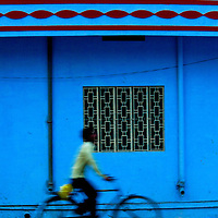 A Young Man Rides Past A Blue House, in Jaipur, Rajasthan, India
