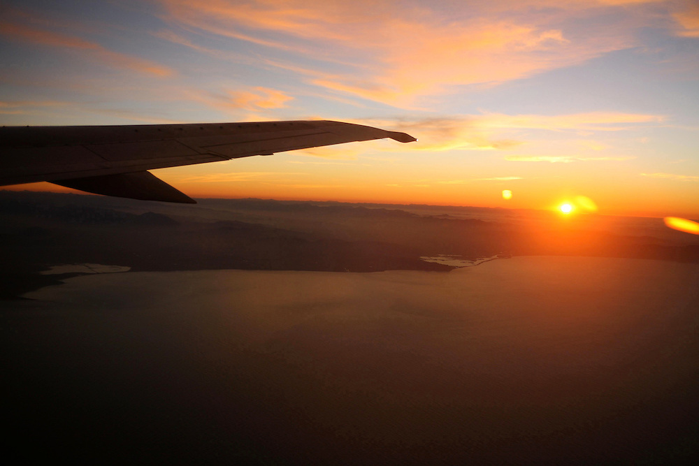 The wing of an Air New Zealand plane silouetted against the setting sun as the plane gains height over Cook Strait heading for Christchurch with the top of the South Island below, May 28, 2007. Credit:SNPA / Rob Tucker