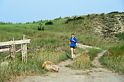 Woman running on a dune trail, Cape Cod, MA