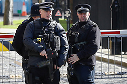 © Licensed to London News Pictures. 25/03/2017. London, UK. Armed police officers stand guard at Black Rod entrance to the Houses of Parliament in Westminster. There is much heightened security around Westminster following a terror attack earlier in the week in which a lone man drove a car over Westminster Bridge, killing and injuring dozens of members of the public, before attacking and killing a police officer. Photo credit: Peter Macdiarmid/LNP