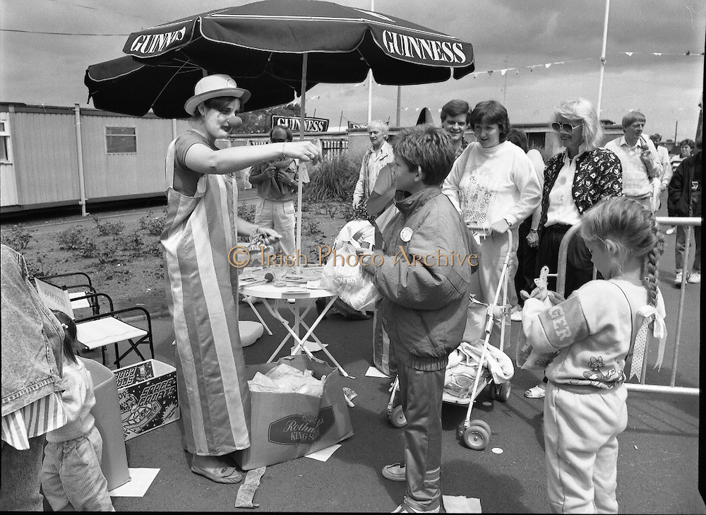 """Guinness Family Day At The Iveagh Gardens. (R83)..1988..02.07.1988..07.02.1988..2nd  July 1988..The family fun day for Guinness employees and their families took place at the Iveagh Gardens today. Top at the bill at the event were """"The Dubliners"""" who treated the crowd to a performance of all their hits. Ireland's penalty hero from Euro 88, Packie Bonner, was on hand to sign autographs for the fans...This clown gets down to the serious business of balloon animal creations for the children at the family day."""