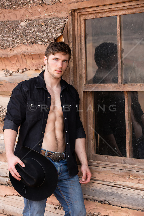 rugged All American cowboy next to a cabin window holding his cowboy hat