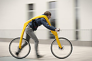 """runaround: The 'Flintstones' bicycle with no pedals or saddle<br /> <br /> It is a design that is sure to turn heads around town<br /> German designers have revealed a bizarre bicycle with no pedals.<br /> Instead, riders are strapped into a harness and move by walking or running<br /> <br /> Called the Fliz, it needs the user to build up speed by running and then lifting their legs to settle on foot rests at the hub of the rear wheel.<br /> Momentum then sends the rider and bike on their way, a little like cartoon stone age man Fred Flintstone's car.<br /> <br /> The bike, created by German designers Tom Hambrock and Juri Spetter, is fixed to the rider with a belt system suspended from the machine's frame under which the rider is fixed into pace.<br /> The bike is an entry into the annual James Dyson Award for technology , innovation and design open to international students and founded by the Dyson vacuum cleaner inventor.<br /> <br /> <br /> FLIZ comes from the German word """"flitzen"""" and means speeding... with your feet.<br /> The concept is to provide healthy, ecological mobility in overcrowded urban spaces.<br /> The frame has a five point belt which is said, despite appearances, to provide a comfortable, ergonomic ride between running and biking. <br /> The belt replaces the saddle and adjusts your position. <br /> The inspiration was the world's first personal transport device , a two-wheeled frame which resembled a modern day cycle but without pedals.<br /> It was built by German inventor Karl Drais and unveiled in 1817.<br /> Known as a velocipede , the student team behind the FLIZ wanted to revive that principle but making it more modern with additional benefits.<br /> The team even tested a replica of the Drais machine to pinpoint it's failings such as th unsafe steering and over large seat.<br /> The FLIZ prototype made of wood and tension belts has been tested.<br /> Entries in the Dyson award compete for a £10,000 top prize.<br /> Hambrock and Spetter h"""