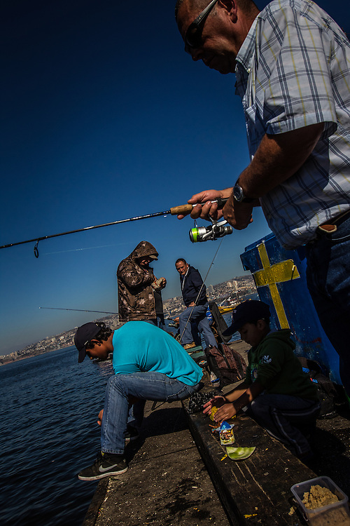 VALPARAISO, CHILE - MARCH 17, 2014: Men fish off of a pier in Valparaiso, Chile. PHOTO: Meridith Kohut for The World Wildlife Fund