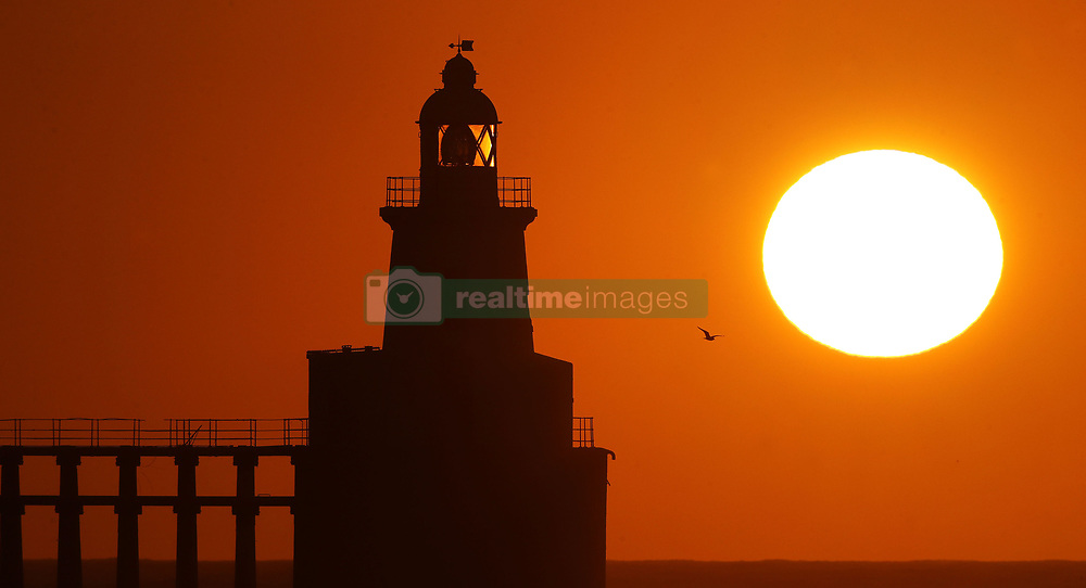 The sun rises over Blyth lighthouse off the Northumberland coast.