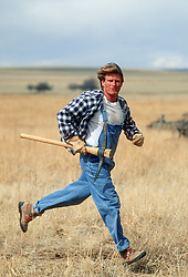rugged man running on a ranch with an axe