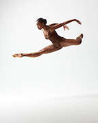 Contemporary female ballet dancer, Sadiya Ramos, jumping in the studio on a white background. Photograph taken in New York City by Rachel Neville.