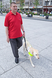 Vision impaired man with guide dog walking along a shopping street,
