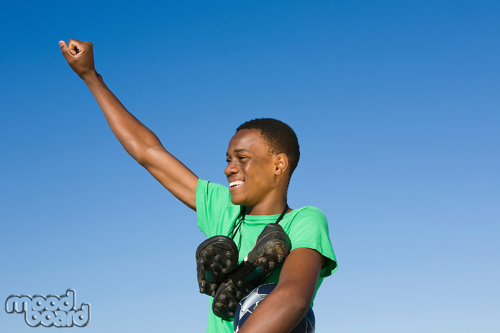 Young man with football boots round his neck and one arm raised in a fist