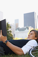 Man lying on lawn reading book close-up