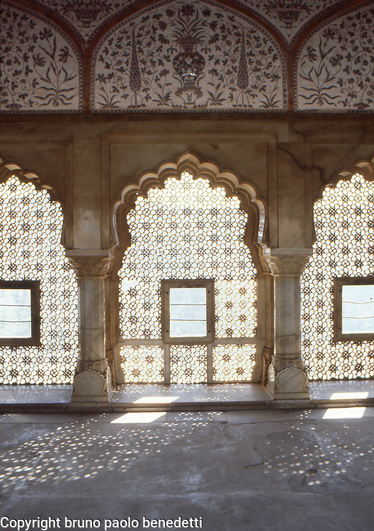 oriental mood:exotic atmoshpere given by these carved windows in Amber Fort in India. The sun light passes through the windows reflecting on the floor lights and windows shapes.