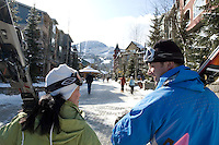 A couple laugh with each other as they walk through Whistler Village carrying their skis on a sunny winter day.