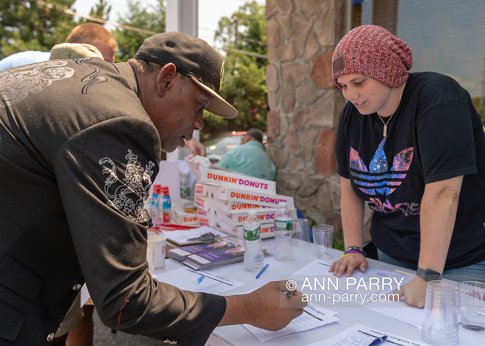 Massapequa, New York, USA. August 5, 2018. Supporter writes his contact info on Volunteer Sign-In sheet, while campaign volunteer looks on, during opening of joint campaign office for Liuba Grechen Shirley, Congressional candidate for NY 2nd District, and NY Senator John Brooks, who are aiming for a Democratic Blue Wave in November midterm elections.
