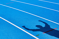 Shadow of an athlete celebrating success in finish line