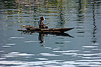 Fisherman in a dugout canoe with an outrigger, Manokwari, West Papua, Indonesia. Manokwari is a small town on the north east coast of the Bird's Head Peninsula, West Papua, Indonesia.  Its harbour has many wrecks from WWII.