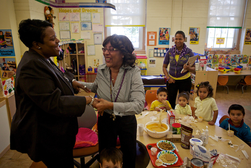 D.C. Public Schools Chancellor Kaya Henderson, left, is greeted by preschool teacher Tilwanda Law at Truesdell Education Campus on Friday, Nov. 16, 2012 in Washington, D.C. Henderson recently announced that she plans to close 20 under-enrolled schools across the district. CREDIT: Lexey Swall for The Wall Street Journal