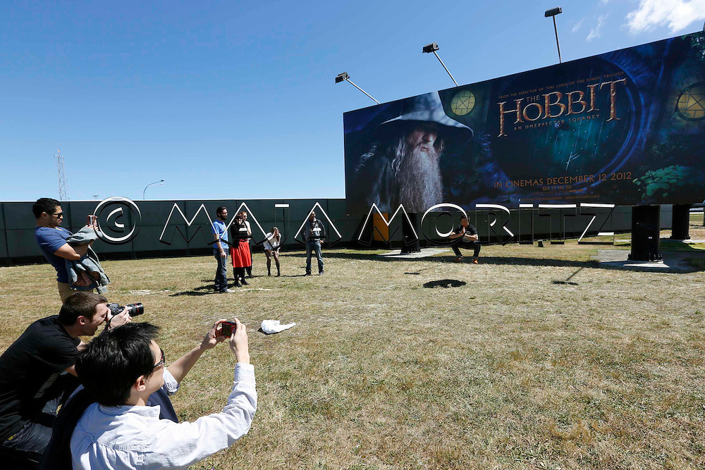 "Employees of the Weta Workshop in Wellington, who have worked on the new Hobbit movie, meet for a photo session in front of a billboard announcing the start of the first movie ""The Hobbit: An Unexpected Journey"" in cinemas for 12 December 2012"