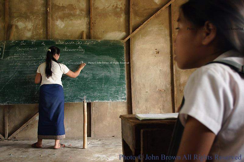 Ban Buamlao Primary School teacher Nang Chanton writes notes on the board as a student observes.  Lacking basic learning utensils, many students find the early years of their public school education in Laos the most difficult according to the faculty members.