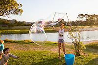Bubbles Festival in Kuaotunu at the reserve . Adults  drink bubbles children blow bubbles. Coromandel Photographer Felicity Jean Photography