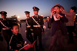 epa02942488 Chinese People's Liberation Army (PLA) officers ushers visitors out of Tiananmen Square as they tale pictures where a giant red lantern is on display for the coming national day at in Beijing, China on 30 September 2011. China will observe the start of the National Day holiday on 01 October, marking the 62nd anniversary of their independence.  EPA/HOW HWEE YOUNG