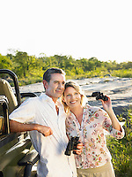 Couple standing by jeep holding binoculars smiling