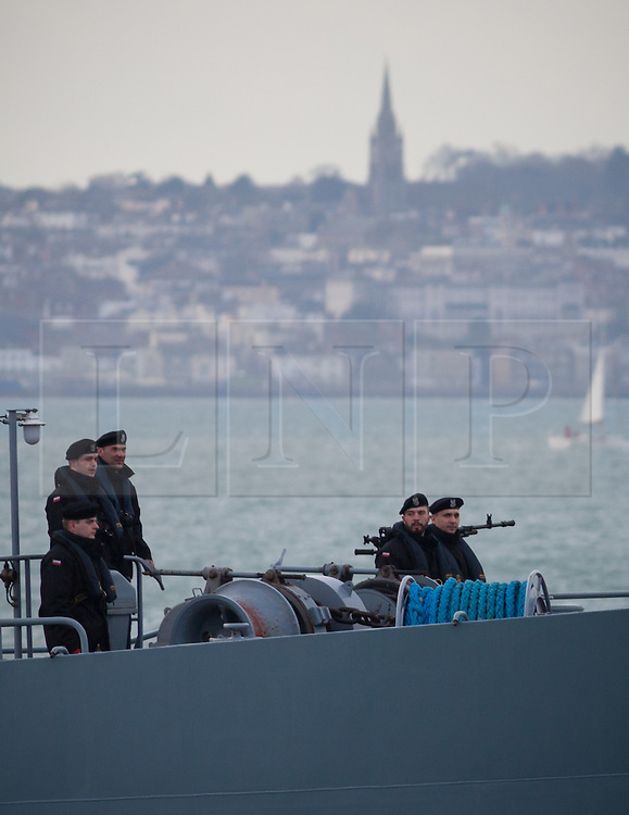 """© Licensed to London News Pictures. 09/01/2017. Portsmouth, UK.  Sailors standing on the bow of the Polish Navy's youngest ship, ORP Kontradmiral Xawery Czernicki, """"Czernicki"""", as she sails into Portsmouth Harbour under Police escort this morning, 9th January 2017. The multi-role support ship is visiting Portsmouth before deploying on a 6-month mission to join Standing NATO Maritime Group 2 (SNMG2) in the Mediterranean Sea. Photo credit: Rob Arnold/LNP"""