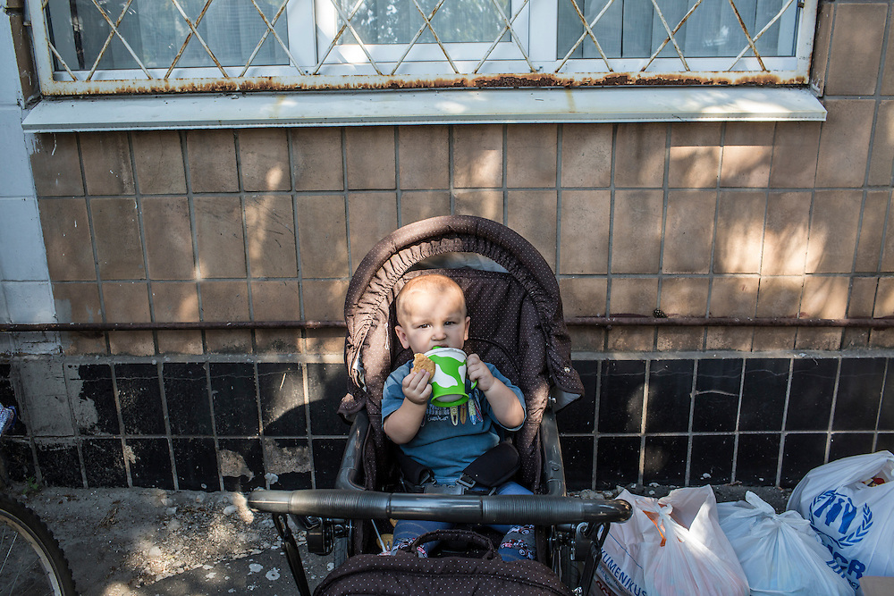SARTANA, UKRAINE - AUGUST 29, 2015: Sasha Morozov, age 15 months, who came with his mother Yana to receive humanitarian assistance in Sartana, Ukraine. The village of Sartana, on the northeastern outskirts of Mariupol, has been relatively close to the front line between Ukrainian and pro-Russian rebel forces, with many incidents of shelling damaging homes and injuring or killing civilians. CREDIT: Brendan Hoffman for The New York Times