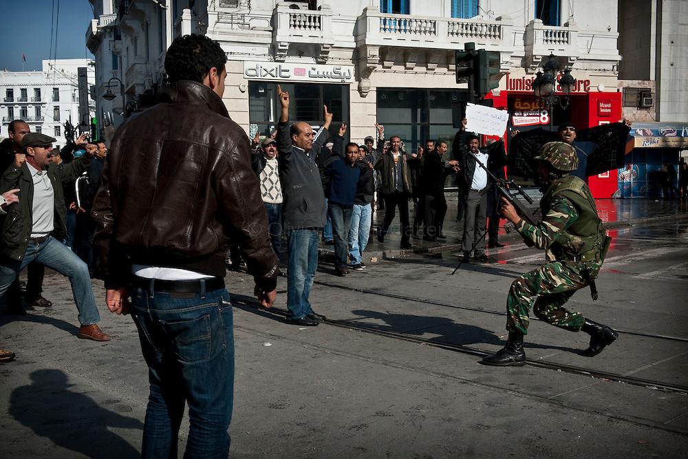 """Un militaire tire en l'air, le 17 janvier 2011 sur l'avenue Bourguiba à Tunis, pour repousser des opposants au régime de Ben Ali venus protester contre la formation du nouveau gouvernement provisoire et réclamer """"le déracinement du système Ben Ali""""."""