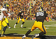 November 23 2013: Iowa Hawkeyes tight end C.J. Fiedorowicz (86) pulls in a 5 yard touchdown pass from Iowa Hawkeyes quarterback Jake Rudock (15) as Michigan Wolverines safety Jarrod Wilson (22) looks on during the first quarter of the NCAA football game between the Michigan Wolverines and the Iowa Hawkeyes at Kinnick Stadium in Iowa City, Iowa on November 23, 2013. Iowa defeated Michigan 24-21.