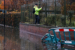© Licensed to London News Pictures. 22/11/2016. Rotherham, UK. A man scales a fence to avoid getting his feet wet on a flooded road in Rotherham, South Yorkshire. Storm Angus has brought heavy wind and rain to much of the UK this week with flooding seen all over. Photo credit : Ian Hinchliffe/LNP