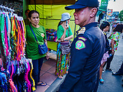 01 AUGUST 2018 - BANGKOK, THAILAND:     A Bangkok code enforcement officer talks to a market vender on Khao San Road in Bangkok. Khao San Road is Bangkok's original backpacker district and is still a popular hub for travelers, with an active night market and many street food stalls. The Bangkok municipal government went through with it plans to reduce the impact of the street market on August 1 because city officials say the venders, who set up on sidewalks and public streets, pose a threat to public safety and could impede emergency vehicles. Venders are restricted to working from 6PM to midnight and fewer venders will be allowed to set up on the street. It's the latest in a series of night markets and street markets the city has closed.    PHOTO BY JACK KURTZ