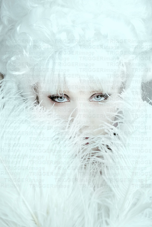 The face of a young woman with blond hair hiding behind feathers