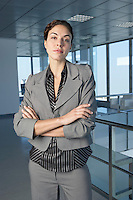 Business woman with arms crossed in office building portrait